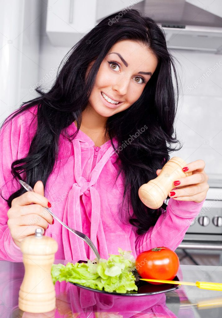 Beautiful young brunette woman eating vegetables in the kitchen at home — Stock Photo #4509586