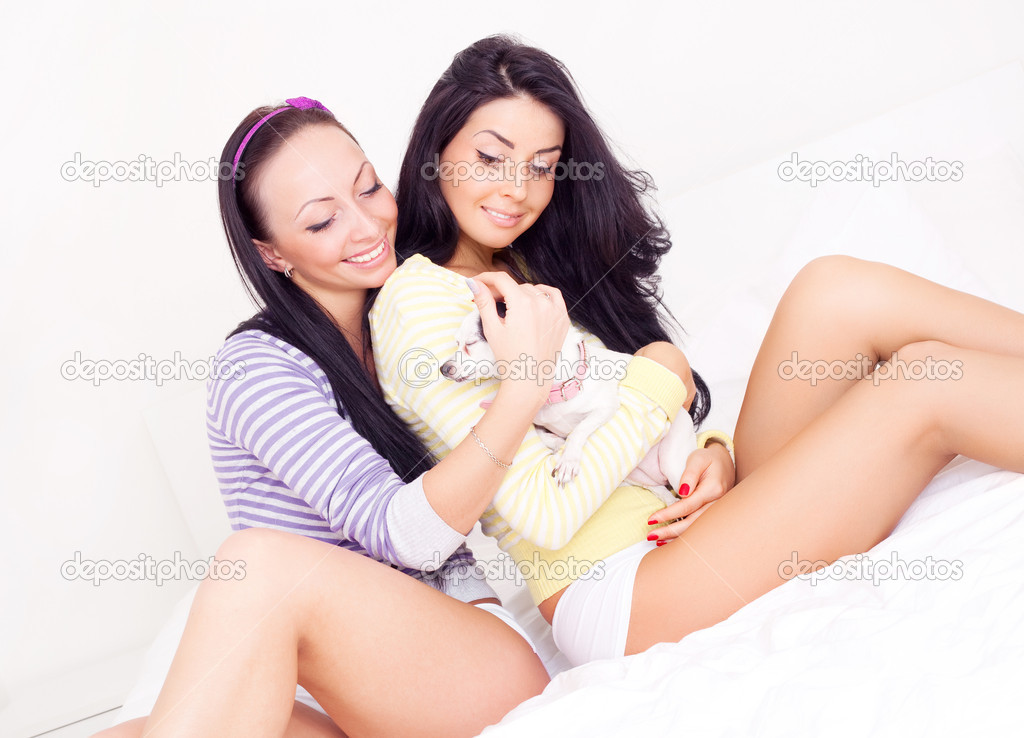 Beautiful  brunette girls with their dog on the bed — Stock Photo #4544204