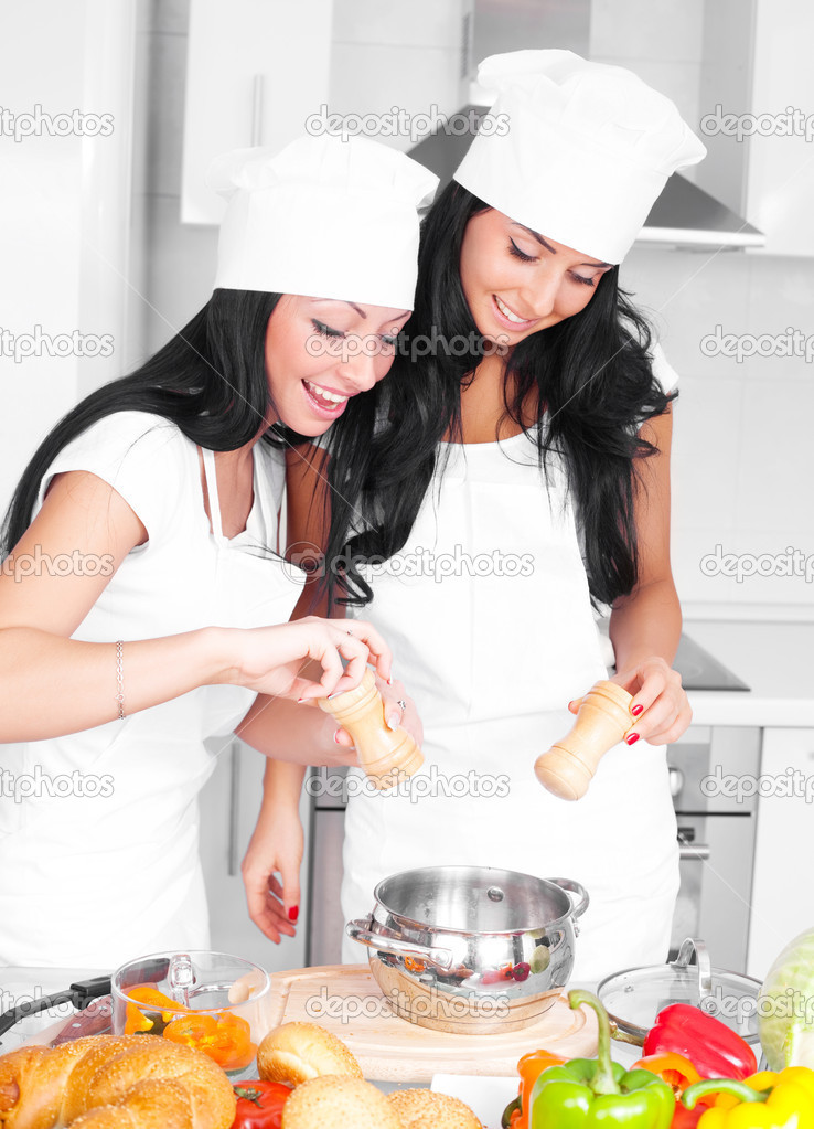 Two beautiful women cooking together in the kitchen at home  Stock Photo #4563037