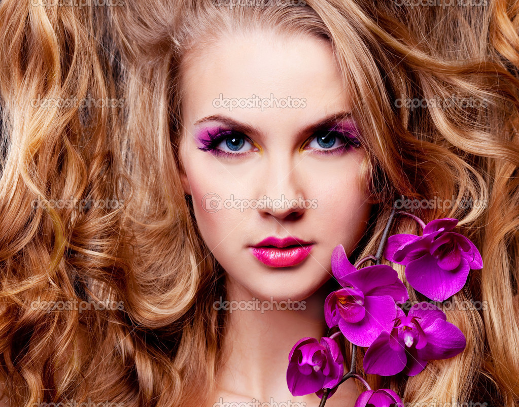 Beautiful young woman with luxurious long curly hair and an orchid — Stock Photo #5105963