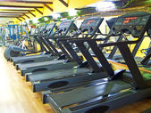 Four treadmills in a row in gym — Stockfoto