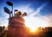 Golf gear, clubs at sunset — Stock Photo