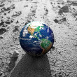 Stock Photo: Earth globe on rocky Mars like surface