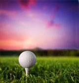 Golf ball on tee at sunset — Stock Photo