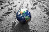 The Earth globe on rocky Mars like surface — Stock Photo