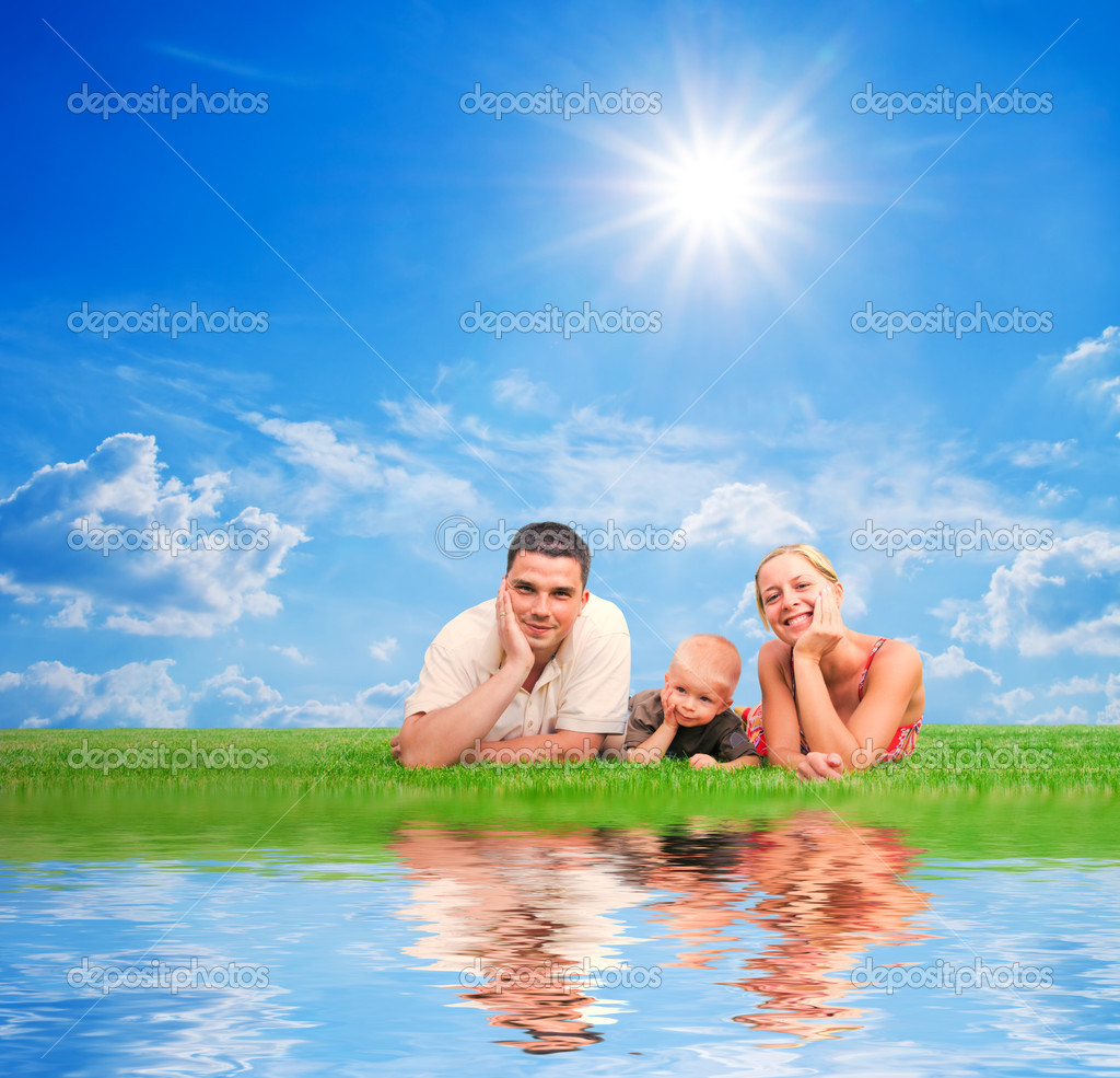 Happy family on grass, sunny sky. Mother, father and a child. — Foto Stock #5201038