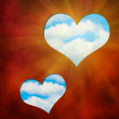 The two hearts cut out in red background against blue sky — Stock Photo