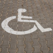 Stock Photo: Handicapped symbol painted on dark asphalt.