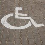 Handicapped symbol painted on dark asphalt. — Stock Photo