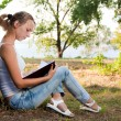 Young woman reading book in the park — Stock Photo