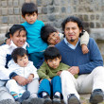 familia latina sentada en la calle — Foto de Stock