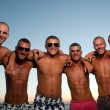 Stock Photo: Joyful team of friends having fun at beach