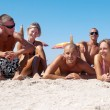 Royalty-Free Stock Photo: Portrait of happy girls and guys lying on sand on summer vacatio