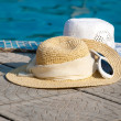 Stock Photo: Straw hats and Sunglasses lies on brink of pool