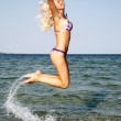 Happy young woman jumping in the beach — Stock Photo