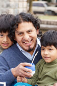 Latin family sitting in the street — Stock Photo