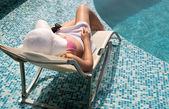 Woman relaxes by the pool — Stock Photo