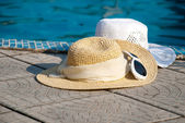 Straw hats and Sunglasses lies on the brink of pool — Stock Photo