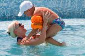 Lächeln, schöne Frau und kleiner Junge badet im pool — Stockfoto