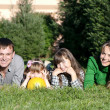 Happy parents and daughters in park — Stock Photo #5350424