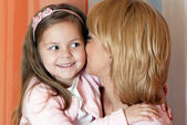 Mother with is whispering with her little girl — Stock Photo