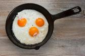 Trzy smażone jajka w patelni na stole — Zdjęcie stockowe