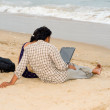 Couple using laptop on the beach - Stock Photo