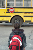 A toddler waiting to catch the school bus — Stockfoto
