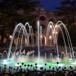 Fountain in front of the ancient roman amphitheatre in Verona, Italy at night - Stock Photo