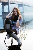 Genç kadın sandalyede siting — Stok fotoğraf