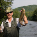 Happy fisherman caught a salmon — Stock Photo