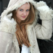 Blond girl in fur coat smiling — Stock Photo