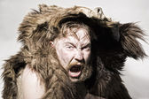 Caveman in bear skin — Stock Photo