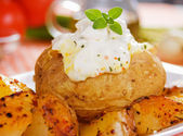 Baked potato with sour cream sauce — Stock Photo