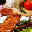 Barbesued ribs with lettuce and lemon slices — Stock Photo