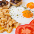 Foto Stock: Fried eggs with beans and mushrooms