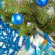 Stock Photo: New Year's still-life - fur-tree branches, a tinsel and a gift box