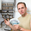 Stock Photo: Sad mcounts money for repair of gas water heater