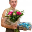 The smiling man with a bunch of flowers and a gift box — Stock Photo