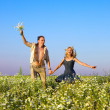 The happy young pair in the field of chamomiles — Stock Photo #4197743