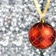 Red New Year's ball on an abstract silvery background — Stock Photo