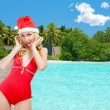 The girl in a bathing suit and a cap of Santa Claus against palm trees - Stock Photo
