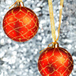 Two red New Year&#039;s balls hang on gold ribbons on a silvery background - Stock Photo