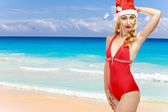 The girl in a bathing suit and a cap of Santa Claus and ocean on a backgrou — Stock Photo