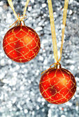 Two red New Year's balls hang on gold ribbons on a silvery background — Stockfoto