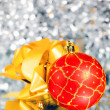 Royalty-Free Stock Photo: Red New Year\'s ball and gold bow on an abstract silvery background