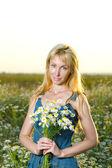 Genç güzel kadın camomiles alanında bir buket — Stok fotoğraf