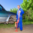 Royalty-Free Stock Photo: The man in working overalls changes a wheel at an off-road car