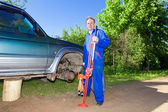 The man in working overalls changes a wheel at an off-road car — Stock Photo