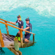 Two persons with the equipment for a snorkeling at steps at ocean. Maldives — Stock Photo #4540152
